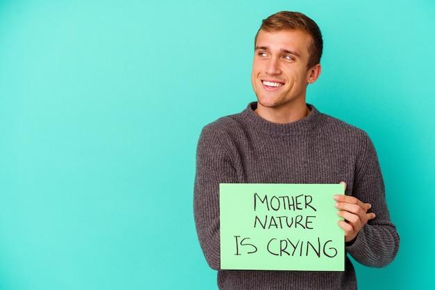 Młody kaukaski mężczyzna trzymający matkę naturę płacze afisz na niebieskim tle, uśmiechając się pewnie ze skrzyżowanymi rękami.