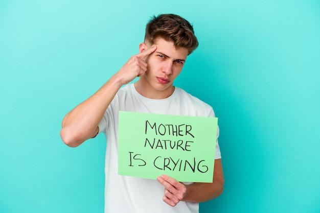 Młody kaukaski mężczyzna trzymający matkę naturę płacze afisz odizolowany na niebieskim tle