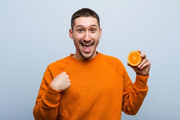 Młody kaukaski mężczyzna trzymający pomarańczę zaskoczony, wskazując na siebie, uśmiechając się szeroko.