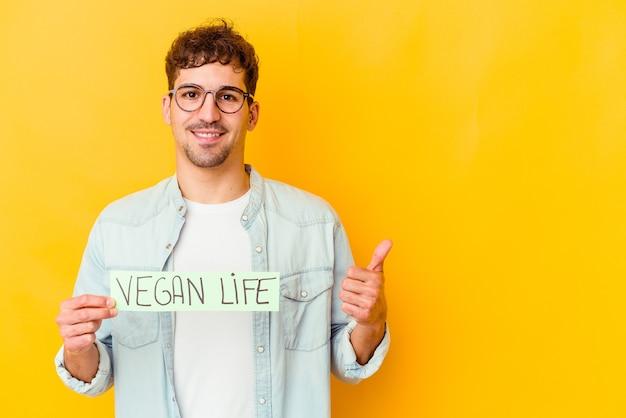 Młody kaukaski mężczyzna trzymający wegański plakat na białym tle uśmiechający się i podnoszący kciuk w górę