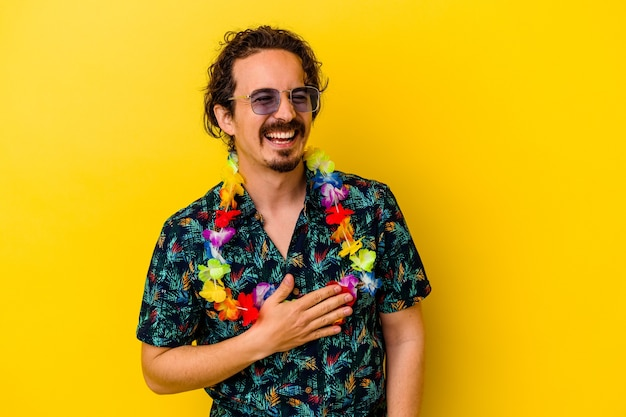 Młody kaukaski mężczyzna ubrany w hawajski naszyjnik na białym tle na żółto śmieje się głośno, trzymając rękę na piersi.