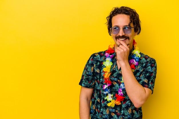 Młody kaukaski mężczyzna ubrany w hawajski naszyjnik na białym tle na żółtym tle zrelaksowany myślenie o czymś, patrząc na przestrzeń kopii.