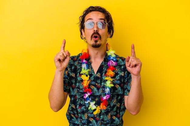 Młody kaukaski mężczyzna ubrany w hawajski naszyjnik na białym tle na żółtym, wskazując do góry z otwartymi ustami.