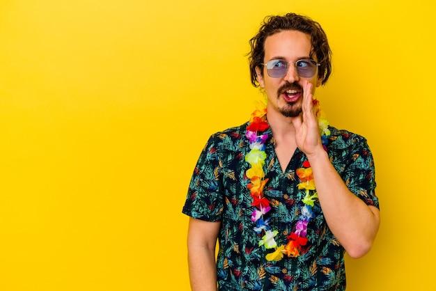 Młody kaukaski mężczyzna ubrany w hawajski naszyjnik odizolowany na żółto, mówi tajną wiadomość o gorącym hamowaniu i spogląda na bok