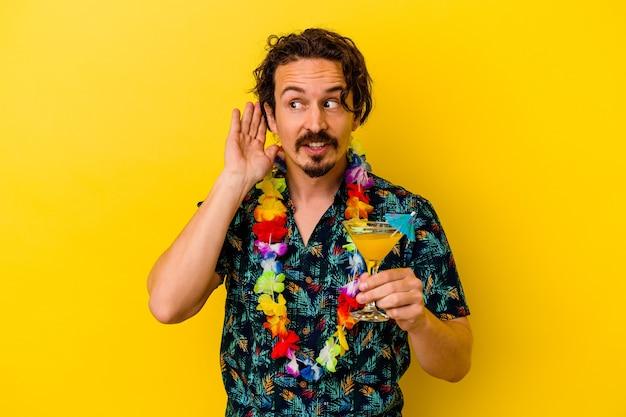 Młody kaukaski mężczyzna ubrany w hawajski naszyjnik trzyma koktajl na białym tle na żółtym tle, próbując słuchać plotek.