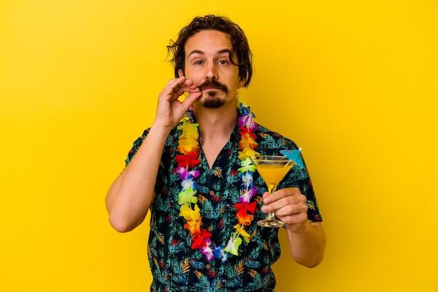 Młody kaukaski mężczyzna ubrany w hawajski naszyjnik trzyma koktajl na żółtej ścianie z palcami na ustach, zachowując tajemnicę
