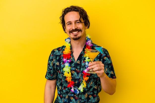 Młody kaukaski mężczyzna ubrany w hawajski naszyjnik trzyma koktajl na żółtym tle szczęśliwy, uśmiechnięty i wesoły.