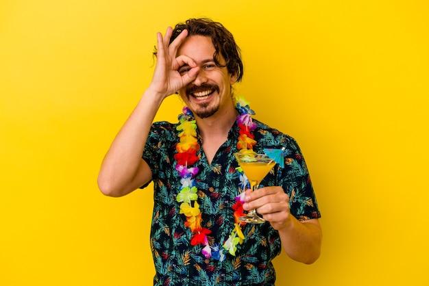 Młody kaukaski mężczyzna ubrany w hawajski naszyjnik, trzymając koktajl na białym tle na żółtym podekscytowany, utrzymując ok gest na oko.