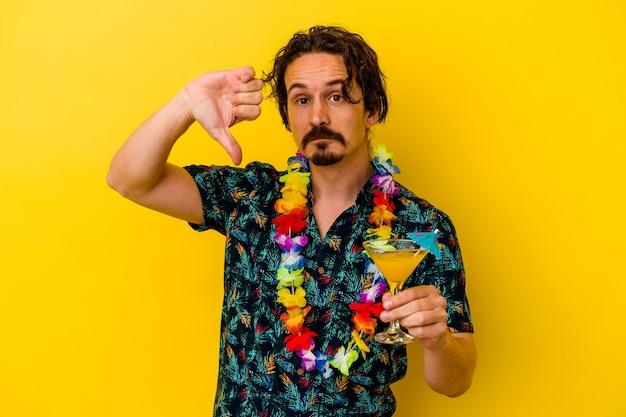 Młody kaukaski mężczyzna ubrany w hawajski naszyjnik, trzymając koktajl na żółtej ścianie, pokazując gest niechęci, kciuk w dół. pojęcie sporu.