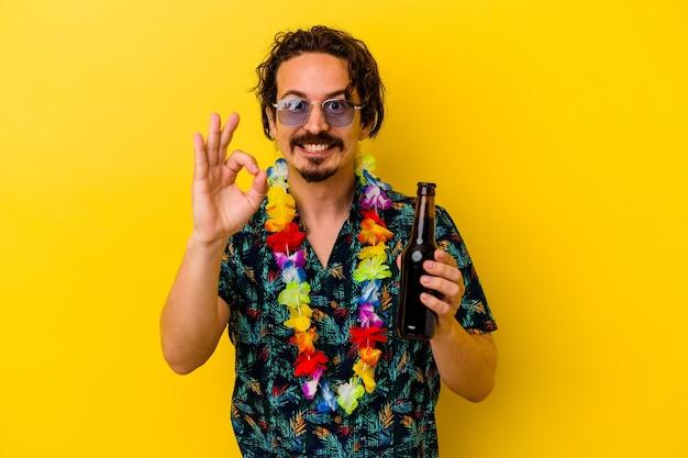Młody kaukaski mężczyzna ubrany w hawajski naszyjnik, trzymając piwo na białym tle na żółtej ścianie, wesoły i pewny siebie, pokazując ok gest