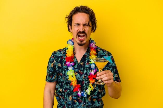 Młody kaukaski mężczyzna ubrany w hawajski naszyjnik trzymający koktajl na żółtej ścianie krzyczący bardzo zły i agresywny