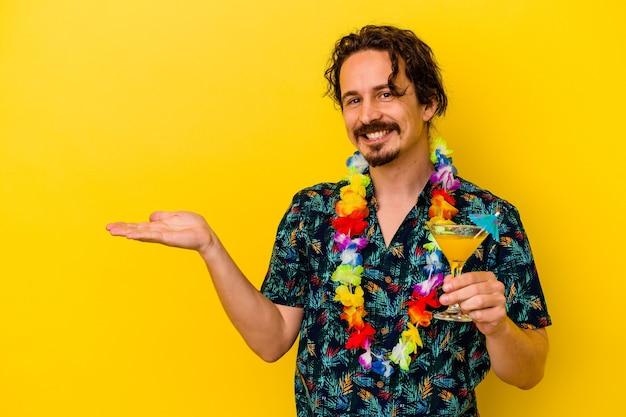 Młody Kaukaski Mężczyzna Ubrany W Hawajski Naszyjnik Trzymający Koktajl Na żółtej ścianie Pokazujący Miejsce Na Kopię Na Dłoni I Trzymający Drugą Rękę Na Talii. Premium Zdjęcia