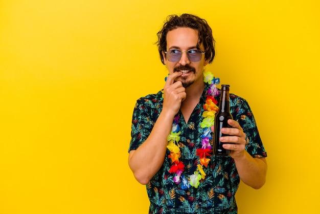 Młody kaukaski mężczyzna ubrany w hawajski naszyjnik trzymający piwo na białym tle na żółtej ścianie zrelaksowany myśląc o czymś, patrząc na przestrzeń kopii.