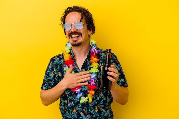 Młody kaukaski mężczyzna ubrany w hawajski naszyjnik trzymający piwo na białym tle na żółtym tle śmieje się głośno trzymając rękę na piersi.