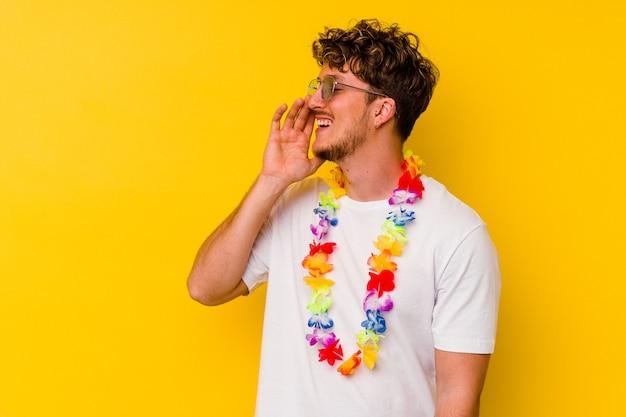 Młody kaukaski mężczyzna ubrany w hawajskie rzeczy imprezowe na białym tle na żółtym tle krzycząc i trzymając dłoń w pobliżu otwartych ust.