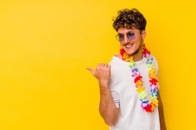 Młody kaukaski mężczyzna ubrany w hawajskie rzeczy na białym tle na żółtym tle wskazuje palcem kciuka, śmiejąc się i beztrosko.