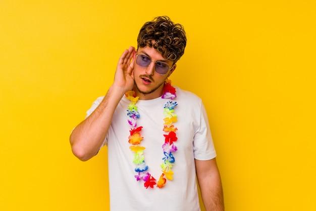 Młody kaukaski mężczyzna ubrany w hawajskie rzeczy na żółtej ścianie, próbując słuchać plotek.