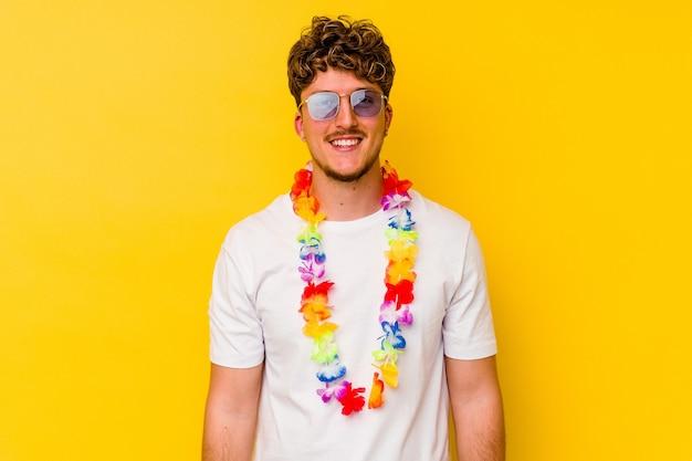 Młody kaukaski mężczyzna ubrany w hawajskie rzeczy na żółtej ścianie szczęśliwy, uśmiechnięty i wesoły.