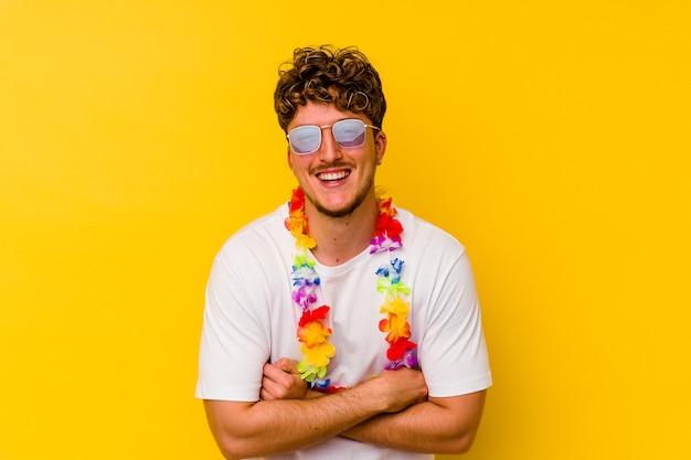 Młody kaukaski mężczyzna ubrany w hawajskie rzeczy strony na białym tle na żółtym tle śmiechu i zabawy.