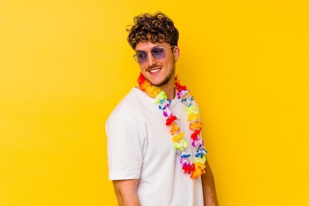 Młody kaukaski mężczyzna ubrany w hawajskie stroje na żółtym tle wygląda z boku uśmiechnięty, wesoły i przyjemny.