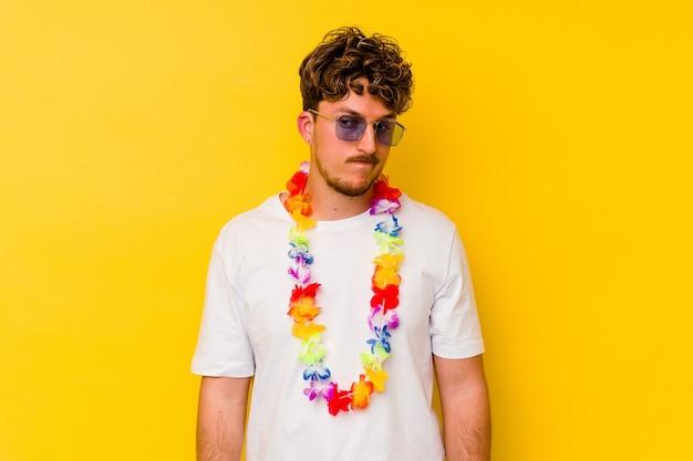 Młody kaukaski mężczyzna ubrany w hawajskie stroje na żółtym tle zdezorientowany, czuje się niepewny i niepewny.