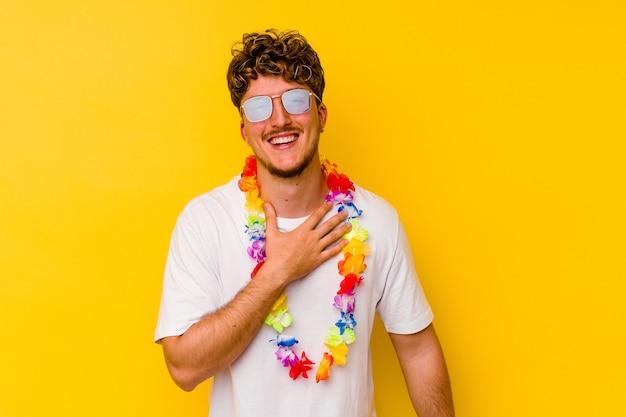 Młody kaukaski mężczyzna ubrany w hawajskie ubrania na żółtej ścianie śmieje się głośno, trzymając rękę na piersi.