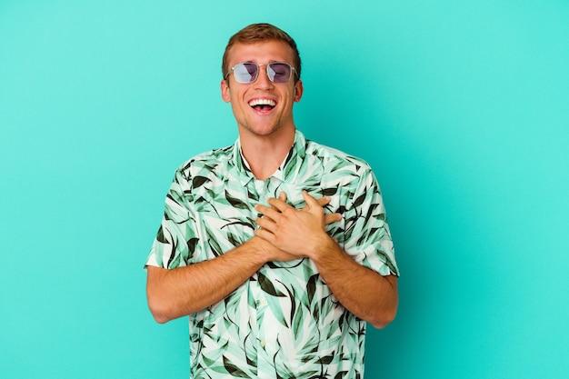 Młody kaukaski mężczyzna ubrany w letnie ubrania na białym tle na niebiesko, śmiejąc się, trzymając ręce na sercu, pojęcie szczęścia.