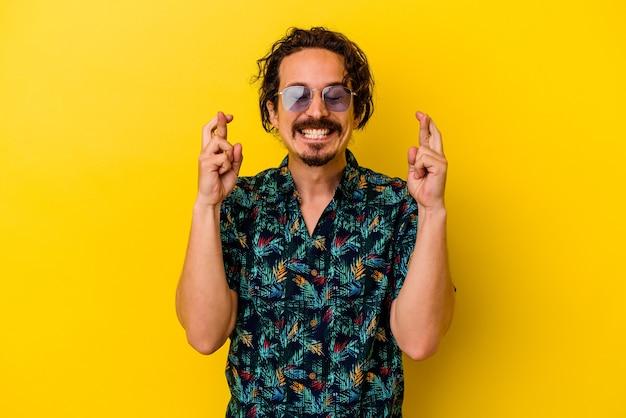 Młody kaukaski mężczyzna ubrany w letnie ubrania na białym tle na żółte skrzyżowane palce na szczęście
