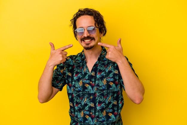 Młody kaukaski mężczyzna ubrany w letnie ubrania na białym tle na żółtej ścianie uśmiecha się, wskazując palcami na usta