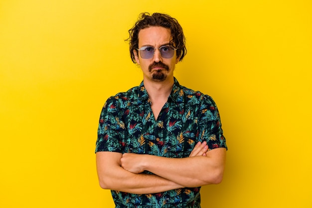 Młody kaukaski mężczyzna ubrany w letnie ubrania na białym tle na żółty niezadowolony patrząc z przodu z sarkastycznym wyrazem.