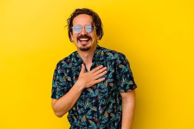Młody kaukaski mężczyzna ubrany w letnie ubrania na białym tle na żółty śmieje się głośno, trzymając rękę na piersi.
