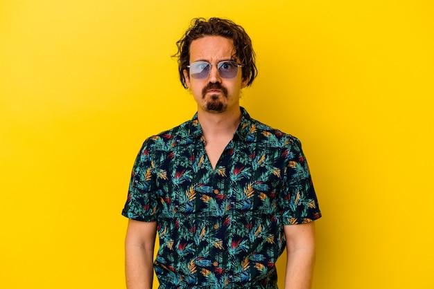 Młody kaukaski mężczyzna ubrany w letnie ubrania na białym tle na żółtym tle dmucha w policzki, ma zmęczony wyraz. koncepcja wyrazu twarzy.