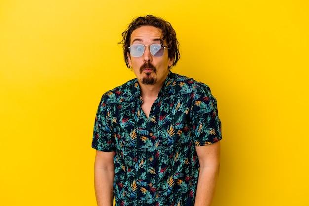 Młody kaukaski mężczyzna ubrany w letnie ubrania na białym tle na żółtym tle wzrusza ramionami i zdezorientowany otwartymi oczami.