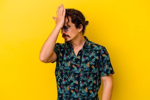 Młody kaukaski mężczyzna ubrany w letnie ubrania na białym tle na żółtym tle zapominając o czymś, uderzając dłonią w czoło i zamykając oczy.