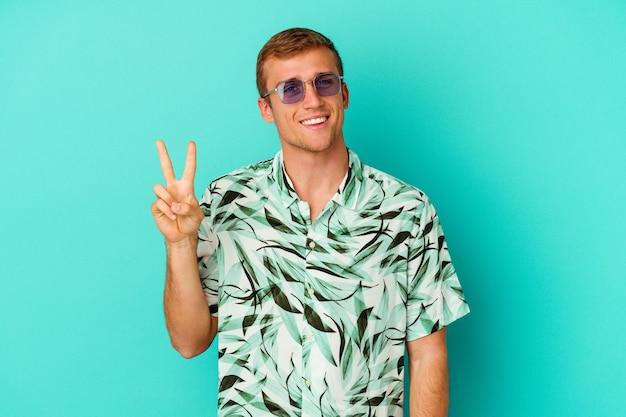 Młody kaukaski mężczyzna ubrany w letnie ubrania na niebieskim tle wyświetlono numer dwa palcami.