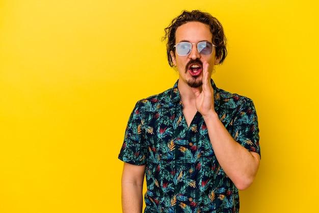 Młody kaukaski mężczyzna ubrany w letnie ubrania na żółtym tle mówi tajną wiadomość o gorącym hamowaniu i patrzy na bok