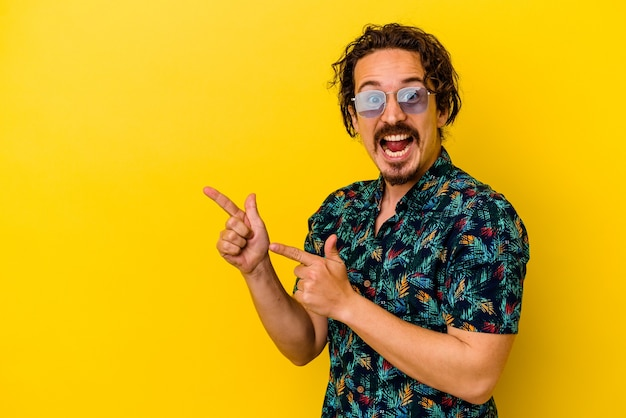 Młody kaukaski mężczyzna ubrany w letnie ubrania odizolowane na żółtej ścianie, wskazując palcami wskazującymi na przestrzeń kopii, wyrażając podekscytowanie i pożądanie.