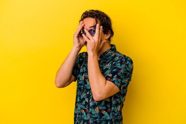 Młody kaukaski mężczyzna ubrany w letnie ubrania odizolowane na żółto mruga przez palce przestraszony i zdenerwowany.