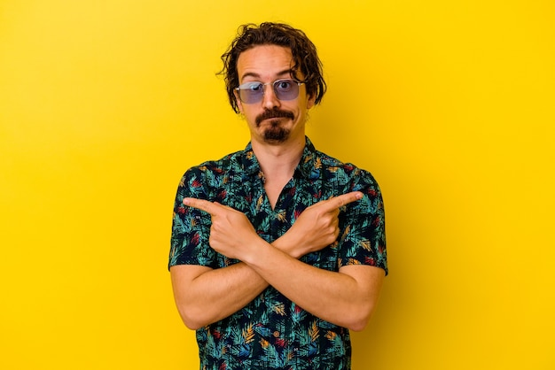 Młody kaukaski mężczyzna ubrany w letnie ubrania odizolowane na żółtych punktach z boku, próbuje wybrać jedną z dwóch opcji.