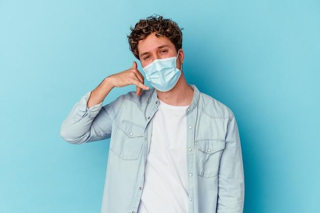 Młody kaukaski mężczyzna ubrany w maskę przeciwwirusową na białym tle na niebieskim tle pokazujący gest rozmowy telefonicznej palcami.
