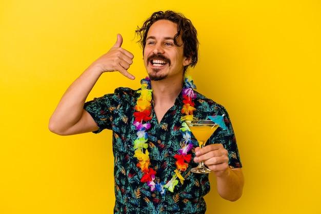 Młody kaukaski mężczyzna ubrany w naszyjnik hawajski trzyma koktajl na żółtym tle pokazujący gest rozmowy telefonicznej palcami.