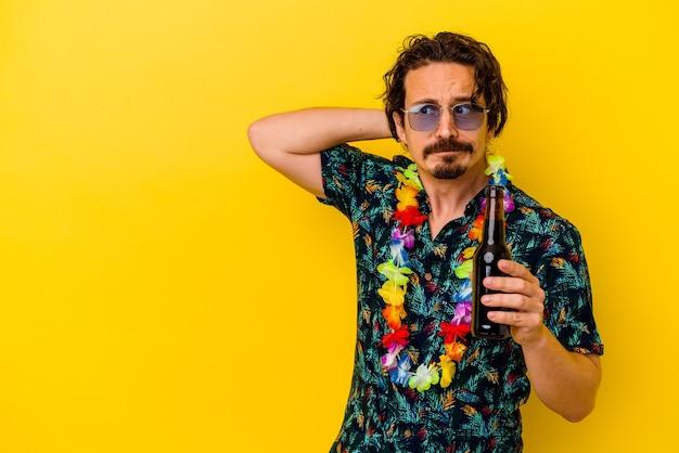 Młody kaukaski mężczyzna ubrany w naszyjnik hawajski trzyma piwo na białym tle na żółtej ścianie dotykając tyłu głowy, myśląc i dokonując wyboru
