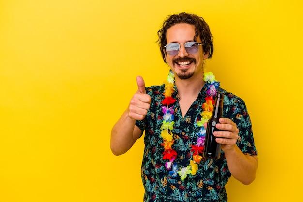 Młody kaukaski mężczyzna ubrany w naszyjnik hawajski trzyma piwo na białym tle na żółty uśmiechnięty i podnoszący kciuk do góry