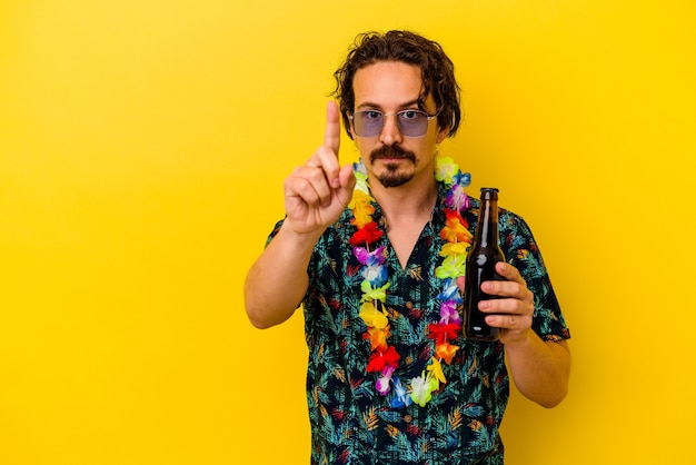 Młody kaukaski mężczyzna ubrany w naszyjnik hawajski trzyma piwo na białym tle na żółtym pokazując numer jeden z palcem.