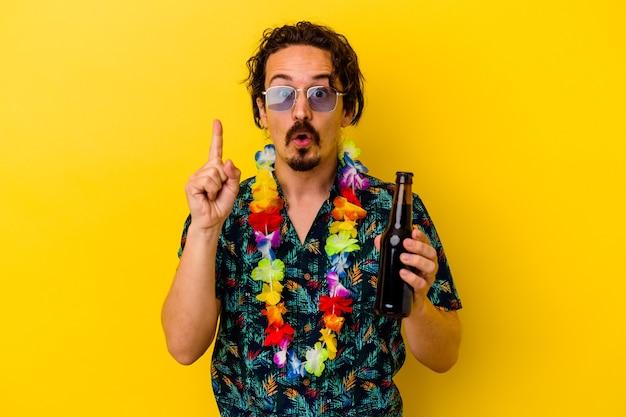 Młody kaukaski mężczyzna ubrany w naszyjnik hawajski, trzymając piwo na białym tle na żółto, mając świetny pomysł, pojęcie kreatywności.