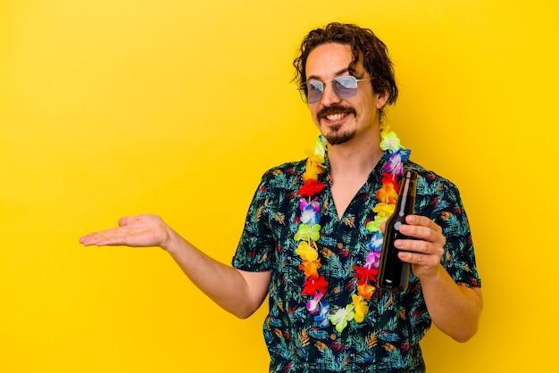 Młody kaukaski mężczyzna ubrany w naszyjnik hawajski trzymający piwo na białym tle na żółtym tle przedstawiający miejsce na kopię na dłoni i trzymający drugą rękę na talii.