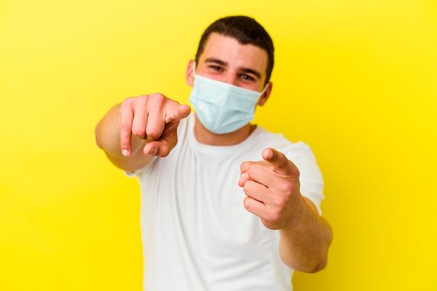 Młody kaukaski mężczyzna ubrany w ochronę przed koronawirusem na białym tle na żółtym tle wesoły uśmiech wskazujący na przód.