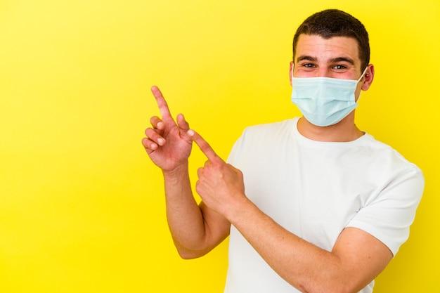 Młody kaukaski mężczyzna ubrany w ochronę przed koronawirusem na białym tle na żółtym tle, wskazując palcami wskazującymi na przestrzeń kopii, wyrażając podekscytowanie i pożądanie.