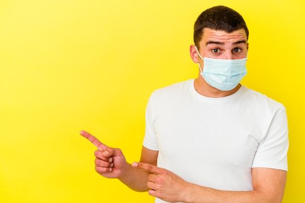 Młody kaukaski mężczyzna ubrany w ochronę przed koronawirusem na białym tle na żółtym tle wstrząśnięty wskazując palcami wskazującymi na miejsce na kopię.