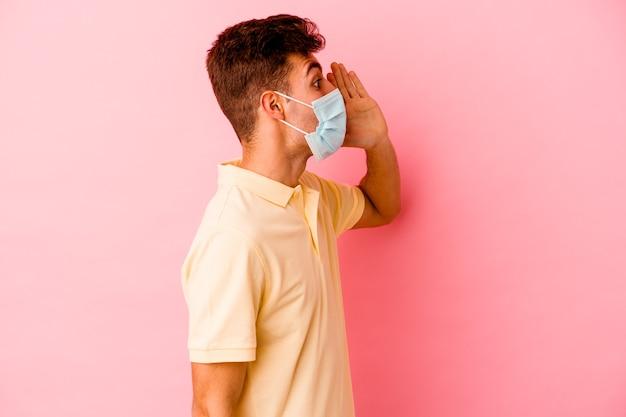 Młody kaukaski mężczyzna ubrany w ochronę przed koronawirusem na różowym tle krzyczący i trzymający dłoń w pobliżu otwartych ust.